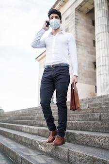 Porträt des geschäftsmannes, der gesichtsmaske trägt und am telefon spricht, während auf treppen draußen steht. unternehmenskonzept. neues normales lifestyle-konzept.
