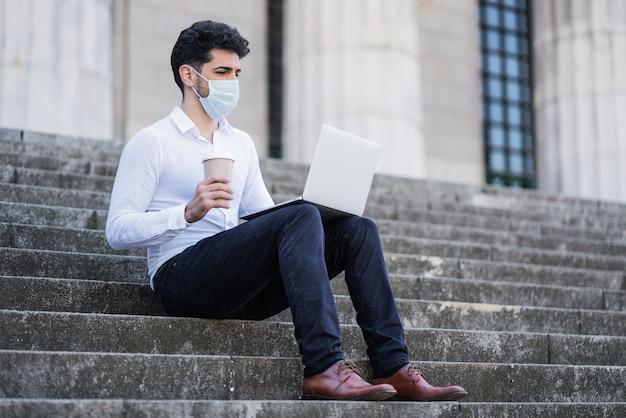 Porträt des geschäftsmannes, der gesichtsmaske trägt und seinen laptop benutzt, während auf treppen draußen sitzt.