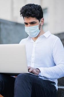 Porträt des geschäftsmannes, der gesichtsmaske trägt und seinen laptop benutzt, während auf treppen draußen sitzt