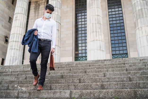 Porträt des geschäftsmannes, der gesichtsmaske trägt und treppe hinuntergeht und aktentasche auf dem weg zur arbeit hält