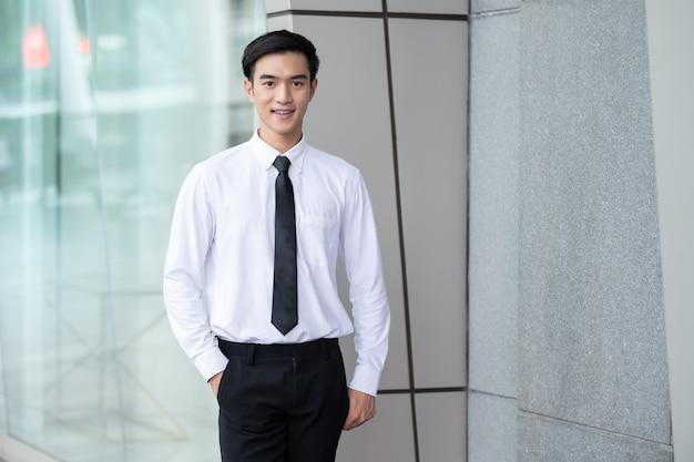 Porträt des geschäftsmannes, des asiatischen jungen mannes im weißen hemd, das im büro im freien lächelt