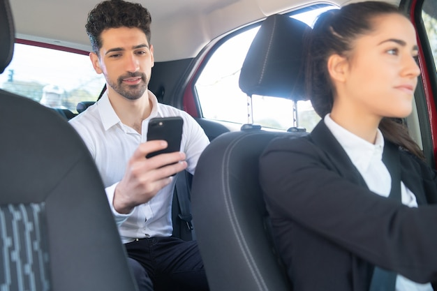 Porträt des geschäftsmannes mit seinem handy auf dem weg zur arbeit in einem taxi
