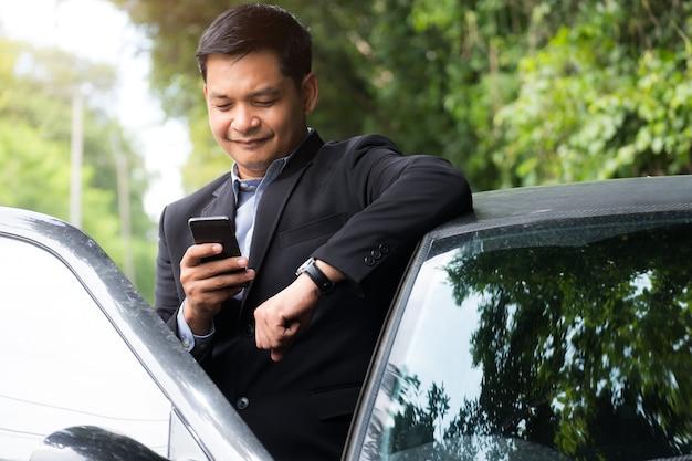 Porträt des geschäftsmanns, der anzug trägt und smartphone mit stehen in der nähe seines autos verwendet