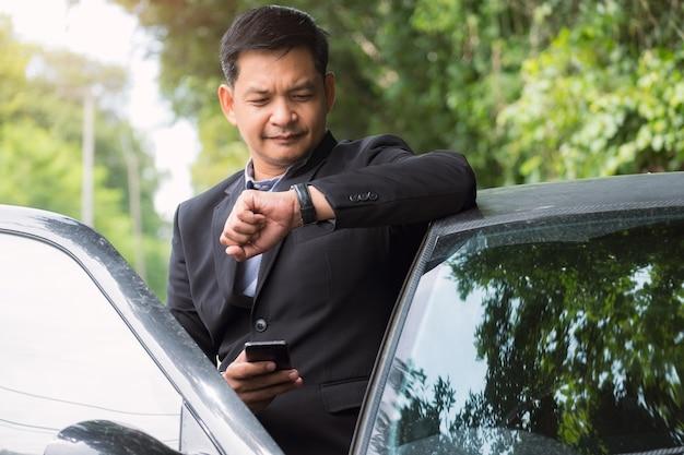 Porträt des geschäftsmanns, der anzug trägt und zeit mit dem stehen nahe seinem auto schaut