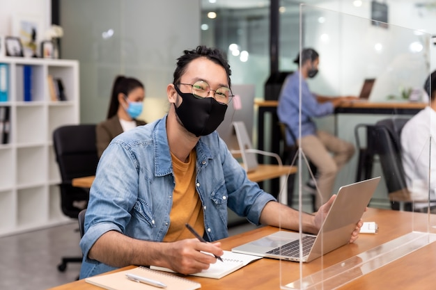 Porträt des geschäftsmanns des asiatischen büroangestellten tragen schützende gesichtsmaskenarbeit in neuem normalem büro mit interracialem kollegen. soziale distanz verhindern coronavirus covid-19.
