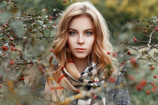 Porträt des gesichtes der jungen schönen frau mit blauen augen in einem modischen grauen mantel in einem weinleseschal auf dem hintergrund eines herbstbaums im wald