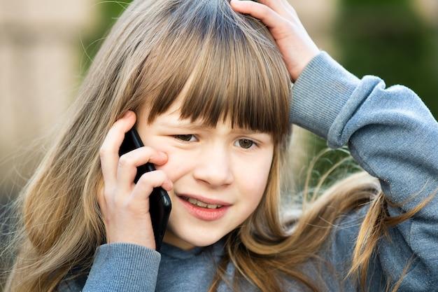 Porträt des gestressten kindermädchens mit den langen haaren, die auf handy sprechen