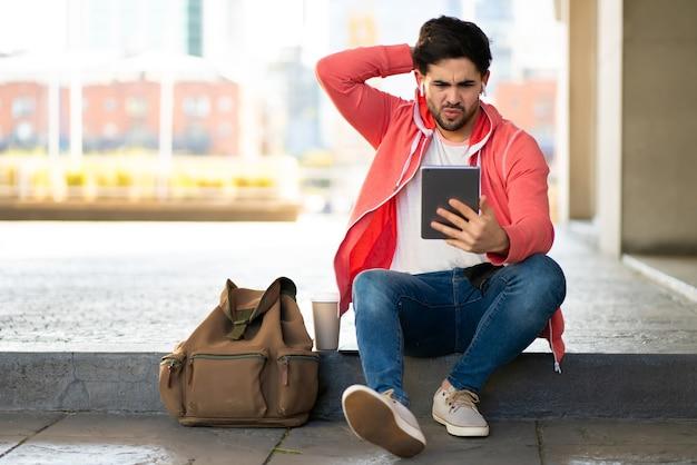 Porträt des gestressten und besorgten mannes, der digitales tablett beim sitzen im freien verwendet. stadtkonzept.
