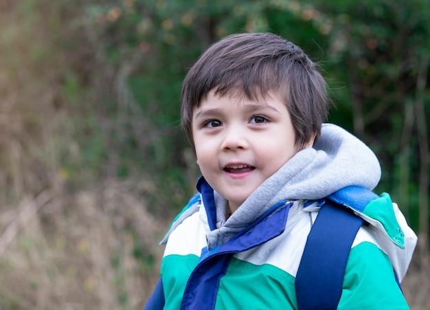 Porträt des gesunden kindes cameara mit lächelndem gesicht betrachtend, ein glückliches kind, das den warmen stoff draußen spielt trägt