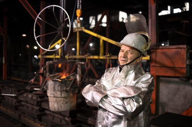 Porträt des gießereiarbeiters, der an heißem geschmolzenem stahl in der produktionsanlage steht.