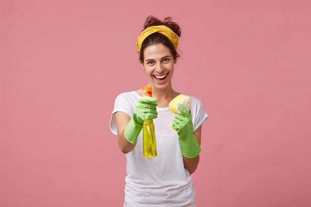 Porträt des glücklich lächelnden dienstmädchens im weißen ordentlichen t-shirt und in den grünen schutzhandschuhen, die ihr waschmittel und schwamm vor der arbeit demonstrieren. konzept für menschen, hausarbeit, haushalt und hausputz