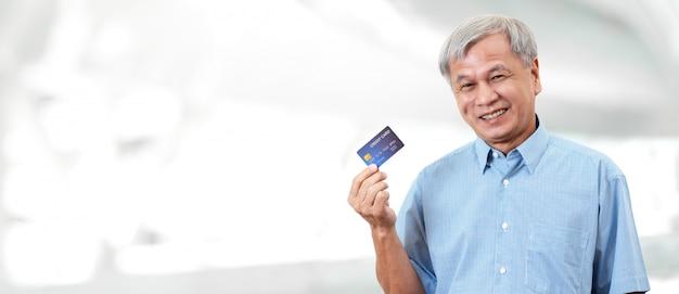 Porträt des glücklichen älteren asiatischen mannes, der kreditkarte hält