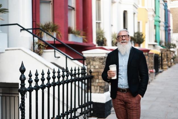Porträt des glücklichen älteren geschäftsmannes, der die straße entlang geht, während eine tasse kaffee hält - fokus auf gesicht