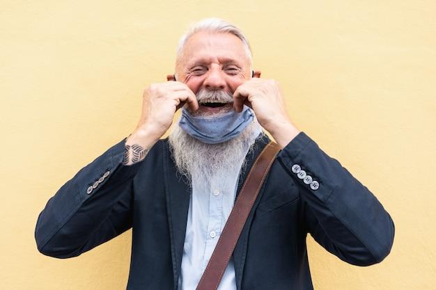 Porträt des glücklichen älteren hipster-mannes mit maske unter kinn