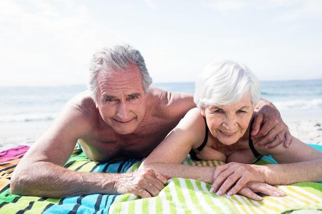 Porträt des glücklichen älteren paares, das am strand liegt