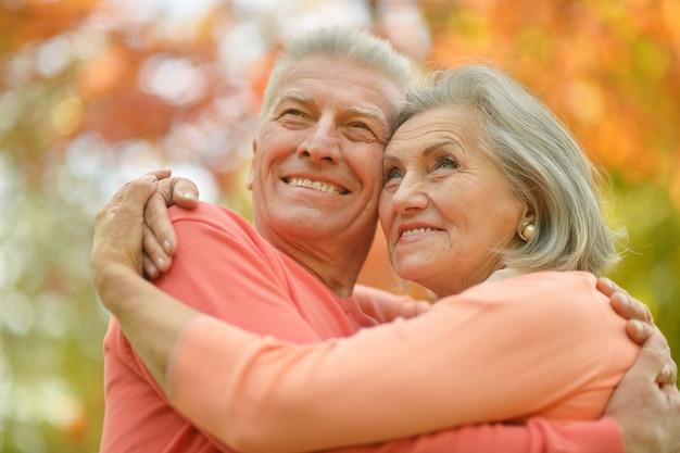 Porträt des glücklichen älteren paares, das im herbstpark umarmt