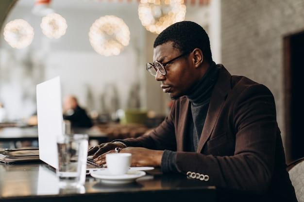 Porträt des glücklichen afrikanischen geschäftsmannes, der an laptop in einem restaurant arbeitet.