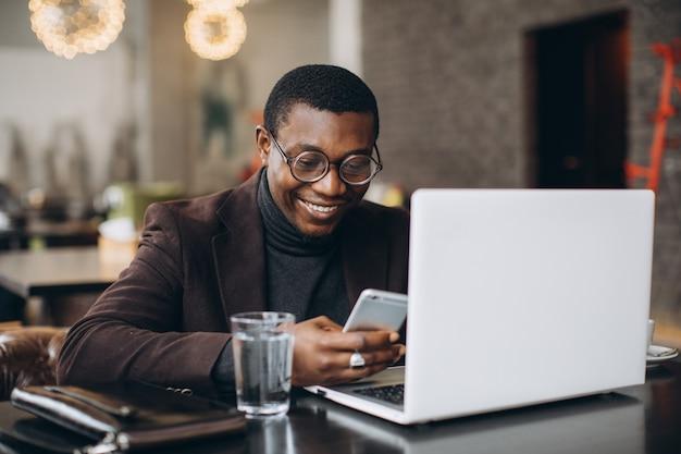 Porträt des glücklichen afrikanischen geschäftsmannes unter verwendung des telefons beim arbeiten an laptop in einem restaurant.