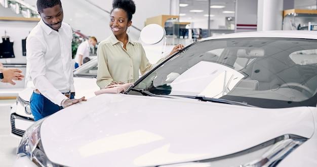 Porträt des glücklichen afroamerikanerpaares, das ein auto im modernen autohaus auscheckt