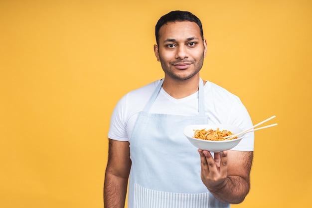 Porträt des glücklichen afroamerikanischen indischen schwarzen mannkochs, der nudeln kocht. kochen, beruf, haute cuisine, essen und menschenkonzept isoliert auf gelbem hintergrund.