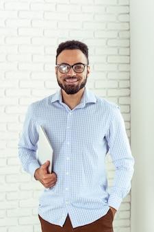 Porträt des glücklichen afroamerikanischen mannes, der laptop comruter verwendet