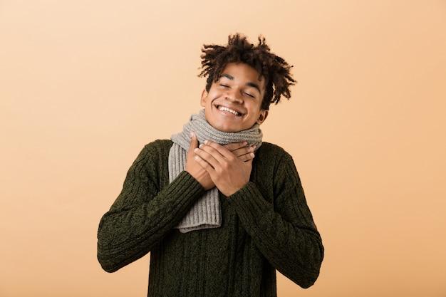 Porträt des glücklichen afroamerikanischen mannes, der pullover und schal trägt, die kehle berühren, lokalisiert über beige wand