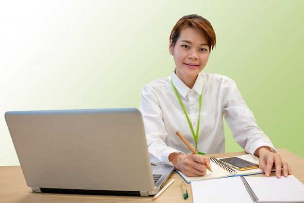 Porträt des glücklichen asiatischen geschäftsfrauschreibensanmerkungsbuches und -laptops mit beschneidungspfad.
