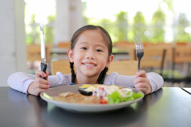 Porträt des glücklichen asiatischen kindermädchens, das auf dem tisch schweinefleischsteak- und -gemüsesalat isst