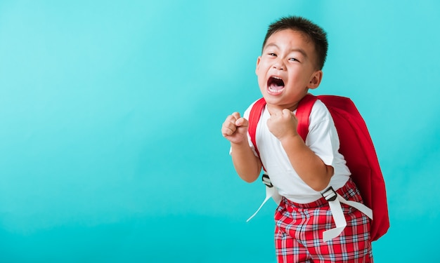 Porträt des glücklichen asiatischen kleinen kinderjungen im einheitlichen lächeln heben hände hoch, wenn sie zurück zur schule gehen