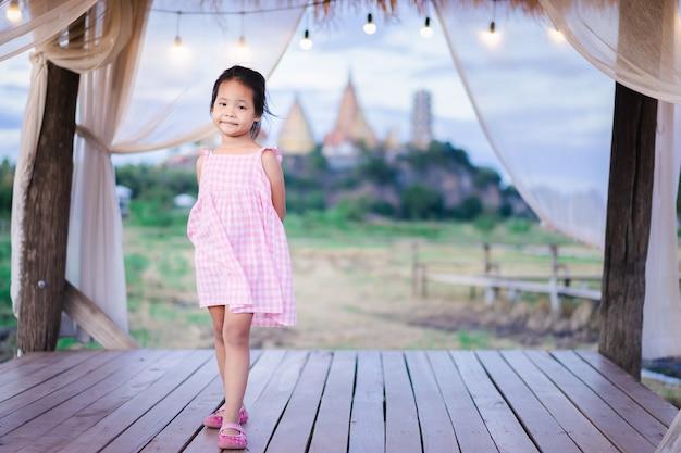 Porträt des glücklichen asiatischen kleinen mädchens im kleid, das auf hölzernem fußweg mit tempel steht