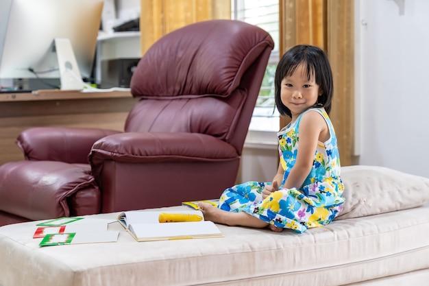 Porträt des glücklichen asiatischen mädchenkindes, das interaktives buch im wohnzimmer zu hause als heimschule liest, während stadt wegen der covid-19-pandemie auf der ganzen welt gesperrt wird. home schooling konzept.