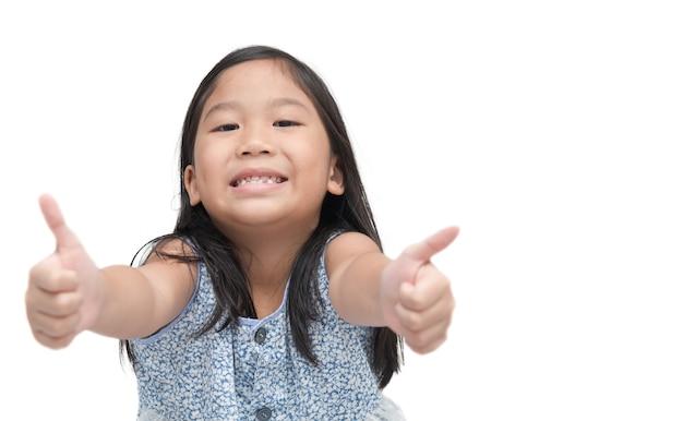 Porträt des glücklichen asiatischen netten mädchens, das daumen zeigt, up geste, lokalisiert über weißem hintergrund