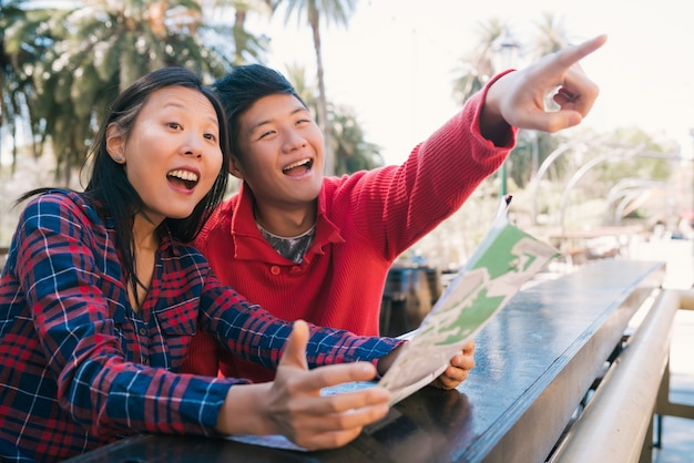 Porträt des glücklichen asiatischen reisendenpaares, das eine karte hält und nach wegbeschreibungen sucht