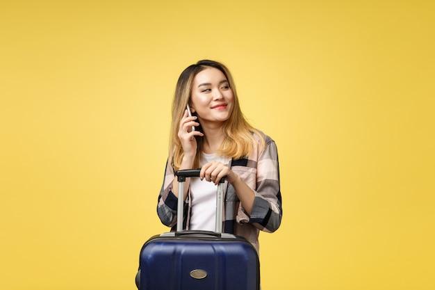 Porträt des glücklichen asiatischen weiblichen reisenden mit koffer und dem betrachten des mobiltelefons
