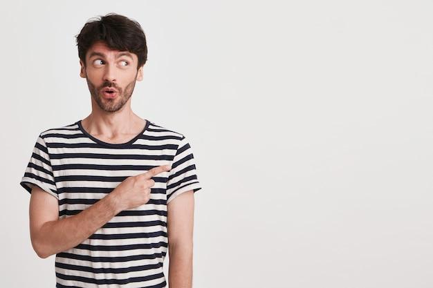 Porträt des glücklichen attraktiven jungen mannes mit borste trägt gestreiftes t-shirt fühlt sich aufgeregt und lächelnd isoliert auf weiß
