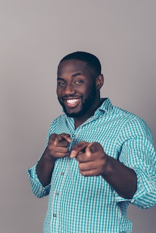 Porträt des glücklichen aufgeregten afroamerikanischen bärtigen mannes, der auf kamera zeigt