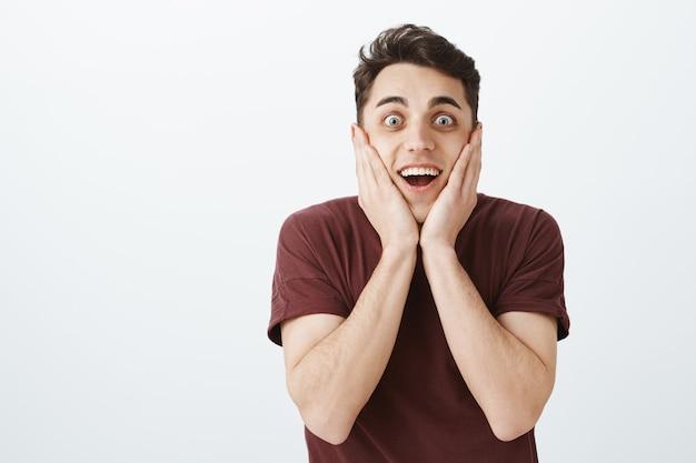 Porträt des glücklichen aufgeregten charmanten kerls im roten t-shirt, die handflächen auf wangen hält und breit lächelt, während überraschende und aufregende dinge sehen