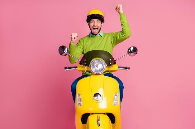 Porträt des glücklichen aufgeregten kerls reitet moped, das sich freut