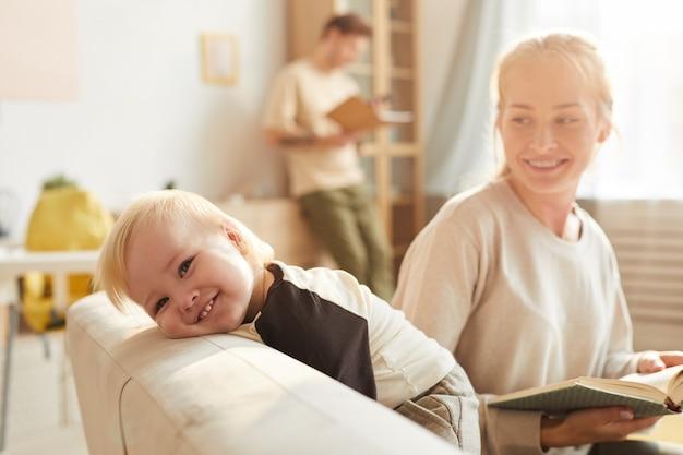 Porträt des glücklichen babys lächelnd, während seine mutter ein buch für ihn auf sofa im wohnzimmer liest