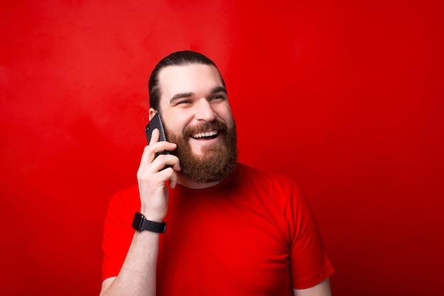Porträt des glücklichen bärtigen mannes, der auf smartphone über rote wand spricht
