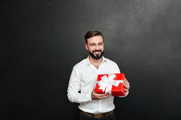 Porträt des glücklichen bärtigen mannes, der rote geschenkbox hält und die kamera über dunkelgrauer wand betrachtet