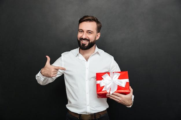 Porträt des glücklichen bärtigen mannes, der rote geschenkbox hält und zeigefinger auf ihr über dunkelgrauer wand zeigt