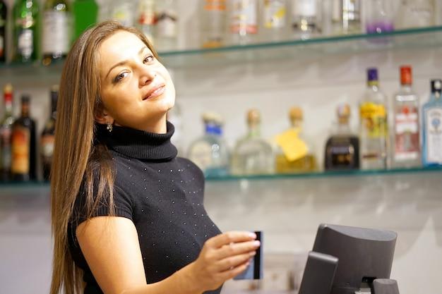 Porträt des glücklichen barkeepers, der neue bestellung durch kasse registriert. ein restaurantangestellter, der eine neue bestellung von cashregister registriert.