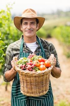 Porträt des glücklichen bauern, der einen korb des gemüses hält