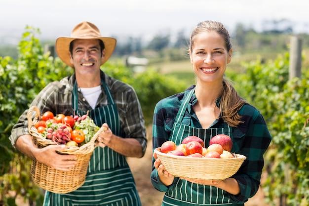 Porträt des glücklichen bauernpaares, das körbe des gemüses und der früchte hält