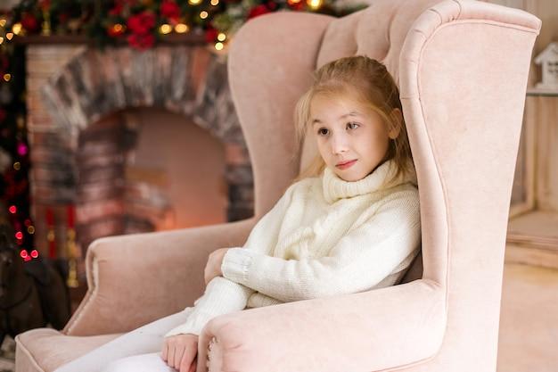 Porträt des glücklichen blonden kindermädchens in der weißen strickjacke, die auf dem boden nahe dem weihnachtsbaum stationiert