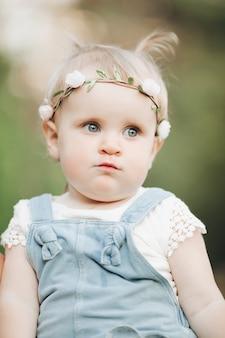 Porträt des glücklichen entzückenden kleinen mädchens im park mit blume auf ihrem kopf. glückliches kindheitskonzept