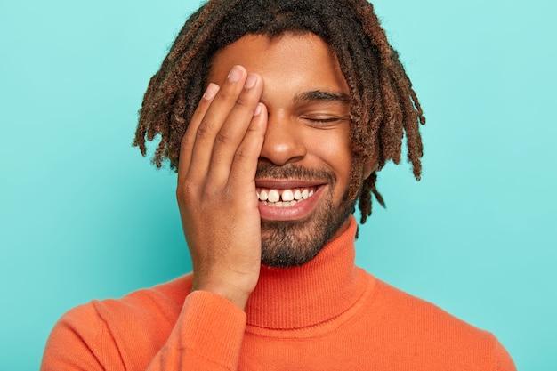 Porträt des glücklichen erfreuten mannes lächelt breit, hat weiße zähne mit kleiner lücke, bedeckt gesicht mit handfläche lacht über lustige situation