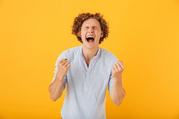 Porträt des glücklichen erstaunten mannes, der fäuste mit geschlossenen augen schreit und ballt, lokalisiert über gelbem hintergrund
