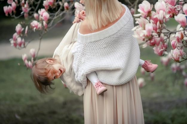 Porträt des glücklichen freudigen kindes in den weißen kleidern über baumblumenblütenhintergrund. familie spielt draußen zusammen. mutter halten fröhlich kleine tochter neugeborenen frühlingskonzept